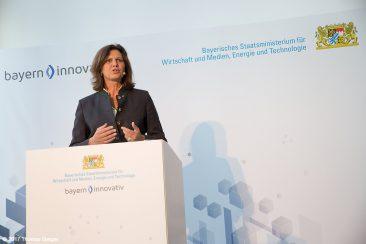 Staatsministerin Ilse Eigner spricht am Rednerpult vor einer hellen Wand