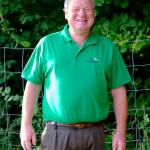 Thomas Schwab halbe Figur im grünen Polohemd, lacht