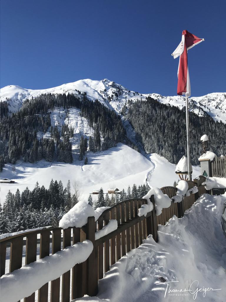 Schneebedeckter Zaun mit Tiroler Fahne vor Bergpanorama