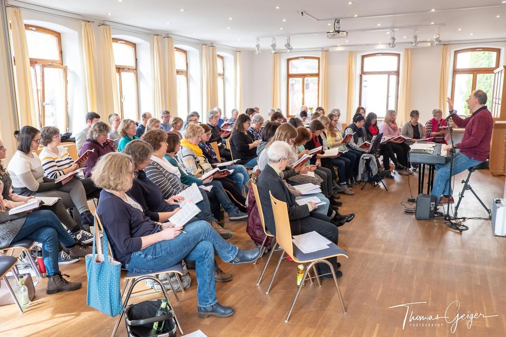 Eine große Gruppe von Menschen, meist Frauen, sitzen in einem Raum mit Liedblättern auf den Knieen. Ein Mann am E-Piano dirigiert