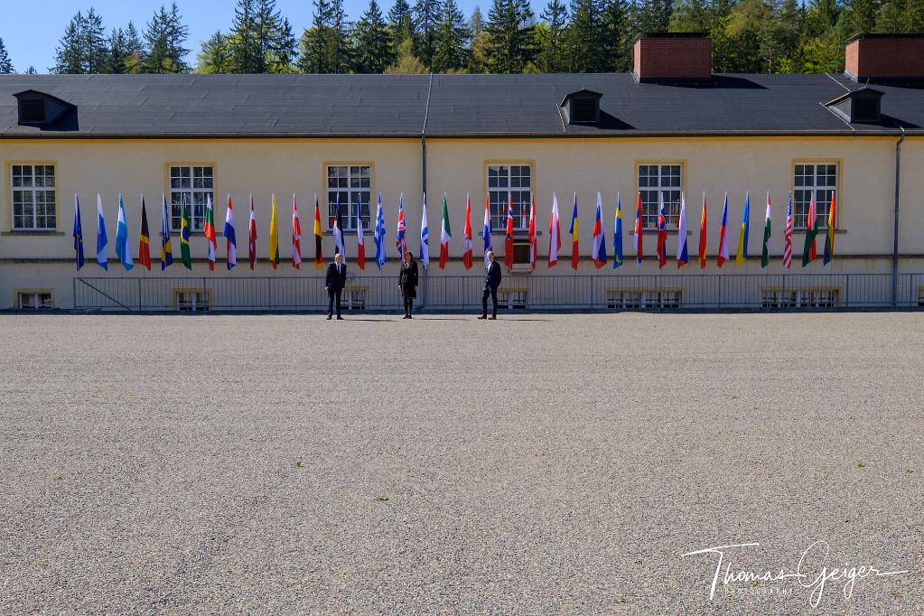 Viele Flaggen auf einem geschotterten Platz davor drei kleine Menschen