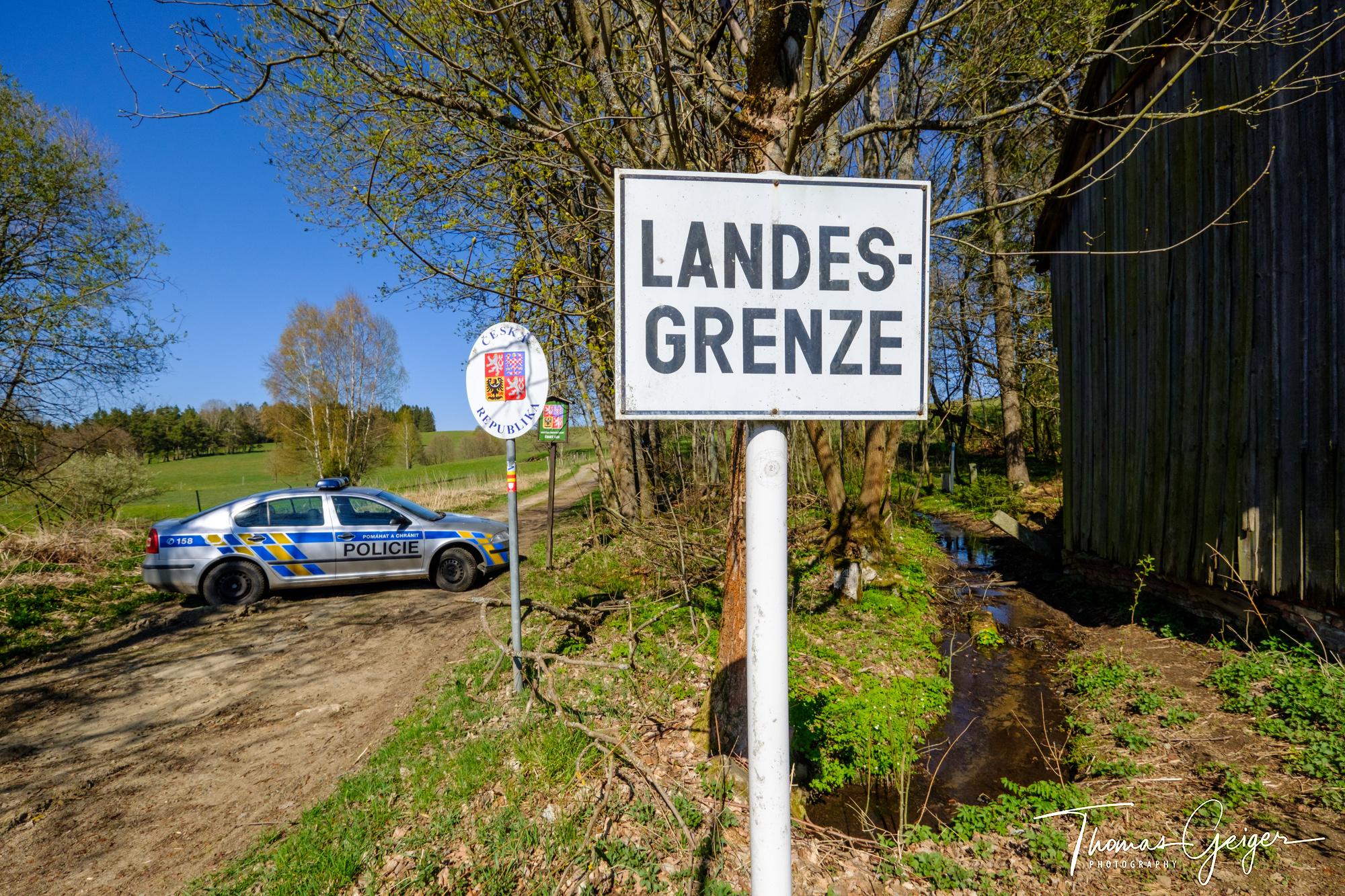 Landschaft mit Feldweg, dieser gesperrt mit einem quergestellten Polizeiauto, Grenzschild Ceska Republika und großes Schild Landesgrenze