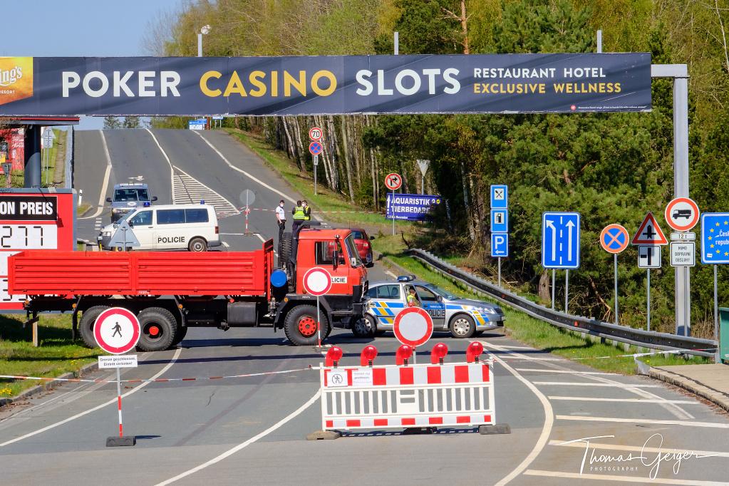 Eine Straße, abgesperrt mit einem roten LKW und einem Polizeiauto, Viele Verkehrsshilder, unter anderem EU Grenzschild Ceska Republika