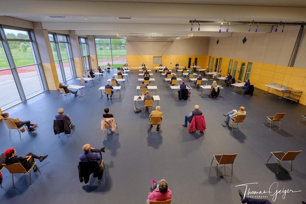 Menschen sitzen vereinzelt in einer großen Turnhalle, zum Teil an Tischen, teilweise ohne