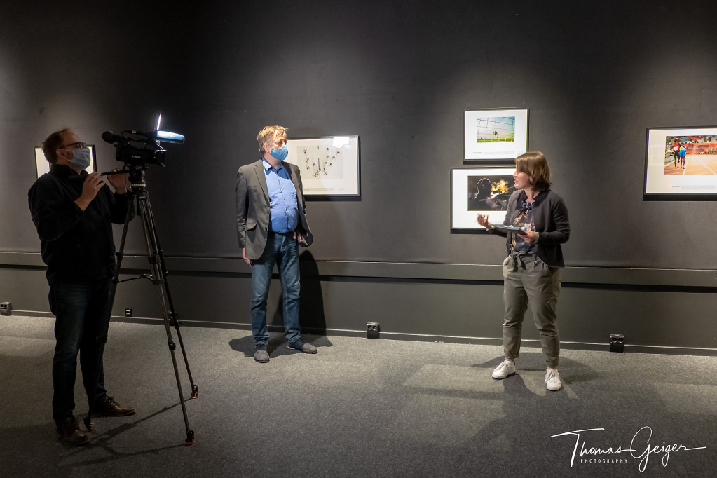 Das Licht einer Fernsehkamera beleuchtet eine Frau und einen Mann, die vor gerahmten Sportfotos an einer schwarzen Wand stehen.