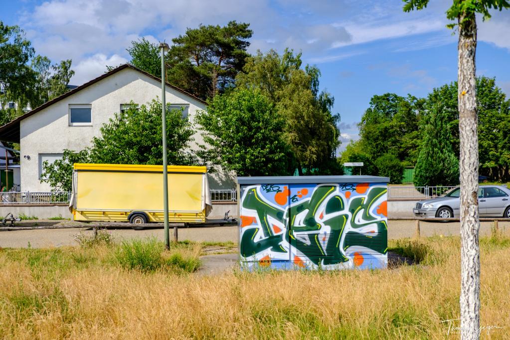 Graffiti auf einem Kasten, trockenes Gras, Laterne an Straße, Wohngebäude, davor gelber Verkaufsanhänger und silberner PKW