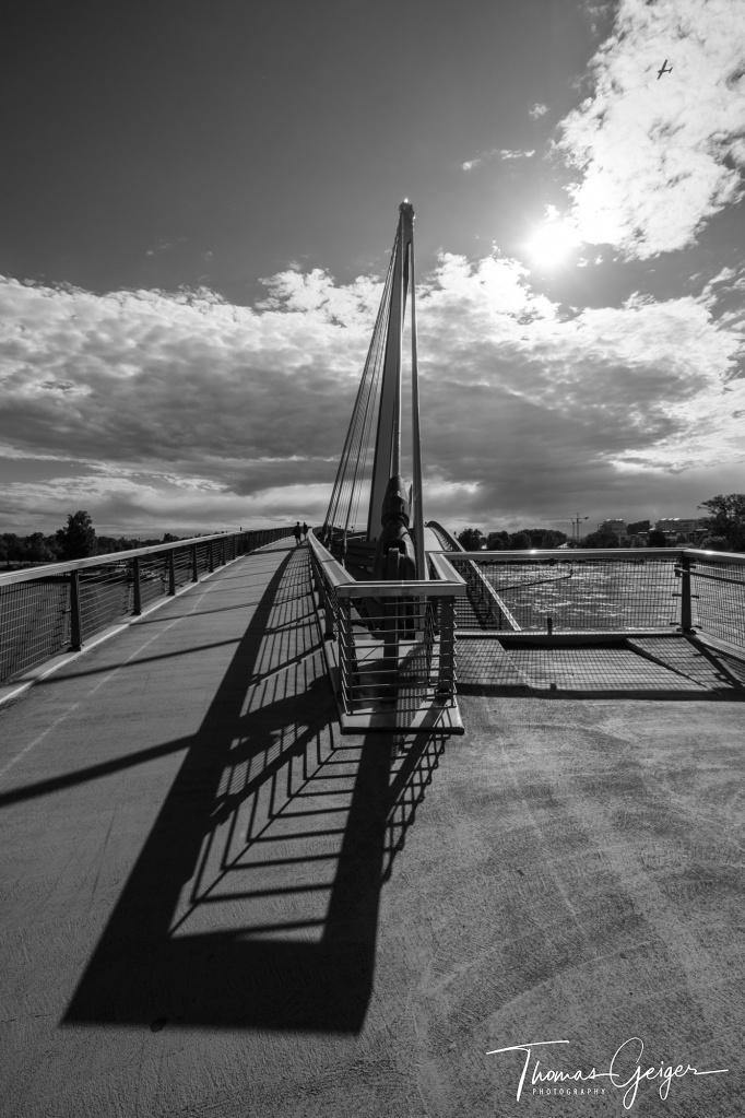 Schwarzweissaufnahme leere Brücke im Gegenlicht, Brückenpfeiler wirft durch die Sonne einen starken Schatten