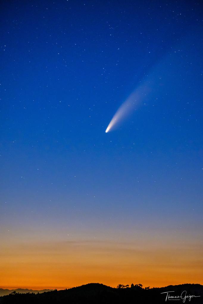 Tiefblauer Sternenhimmel mit einem Kometen, nach unten letztes Orangenes Licht über dem Horizont, der im rechten Drittel die Silhouette einer Burg zeigt