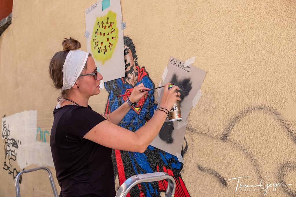 Junge Frau sprayt mit Spraydose an einer Wand einen Drosten im Superman-Kostüm