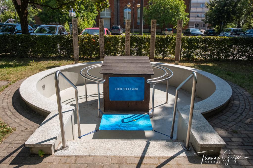 """Leeres Kneipp-Becken mit zwei Bildern, eines symbolisiert Wasser, das andere zeigt nur den Text """"HIER FEHLT WASser"""""""
