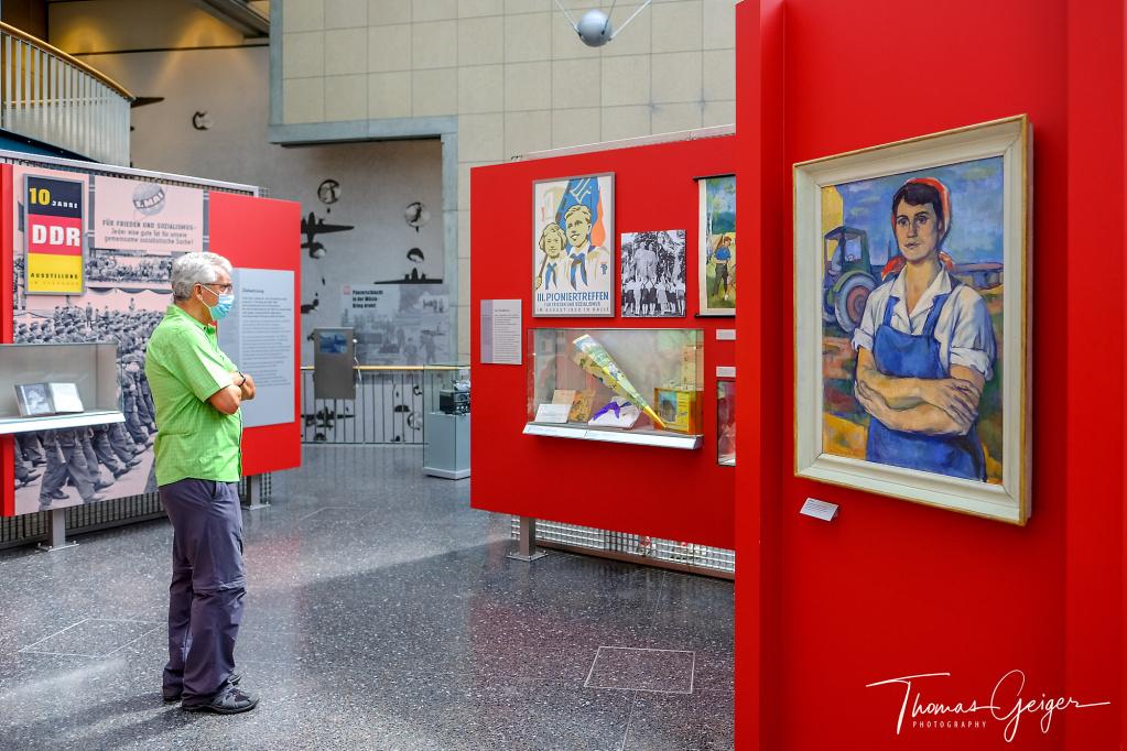 Mann mit Maske und verschränkten Armen steht vor einem Gemälde einer Frau mit verschränkten Armen.