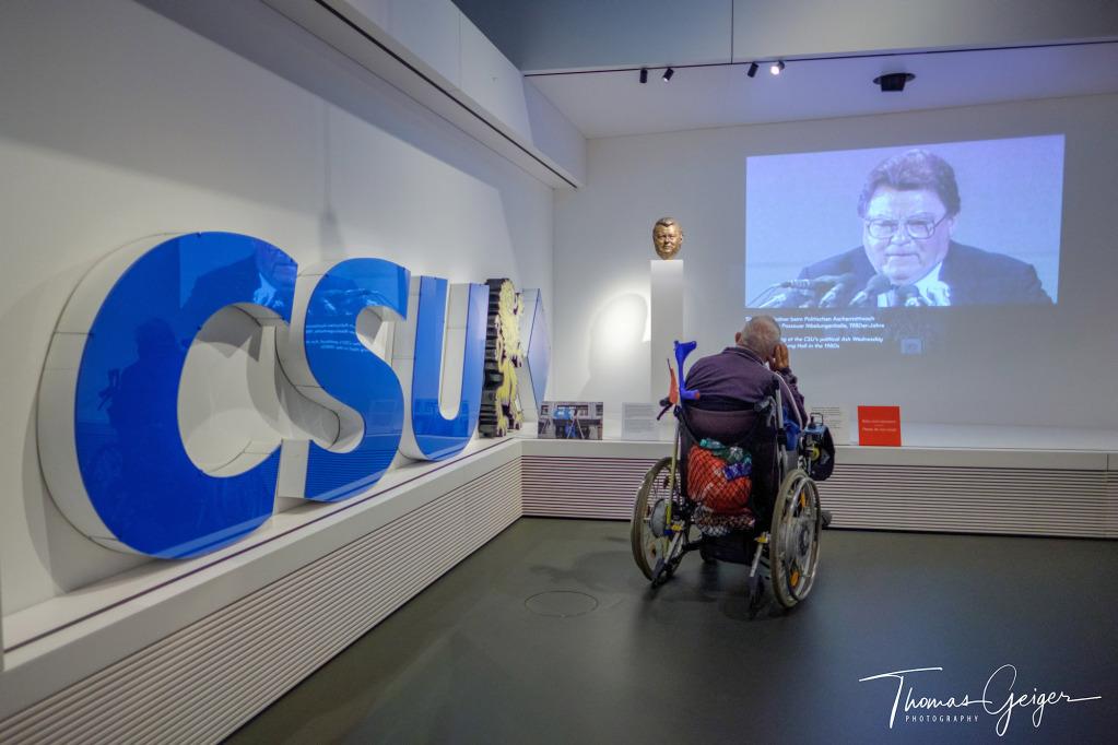 Mann im Rollstuhl betrachtet Video und Büste von Franz-Josef Strauß, links groß blaue CSU Buchstaben