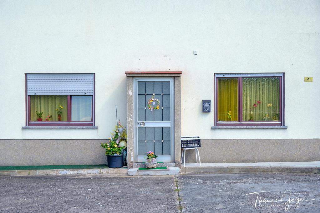Alutür mit Dekoration, links und rechts ein Fenster mit Blumen