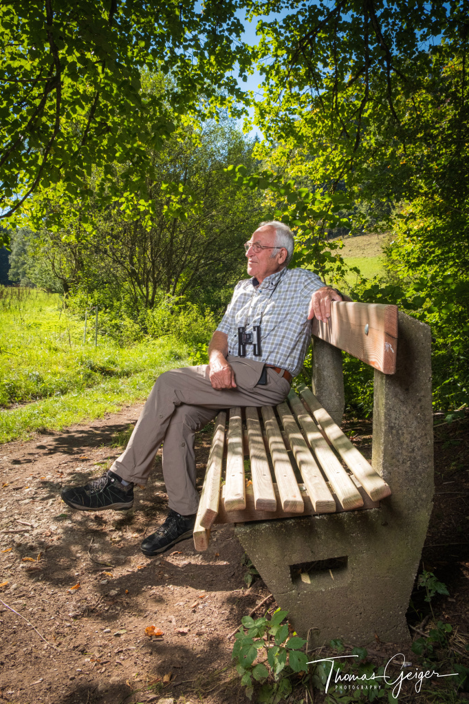Älterer Mann mit Fernglas um den Hals sitzt entspannt auf einer Bank und schaut in die Landschaft