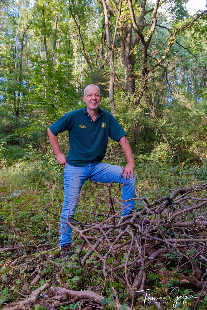Ein Mann mit Jeans und Polohemd steht auf einer kleinen Lichtung im Wald