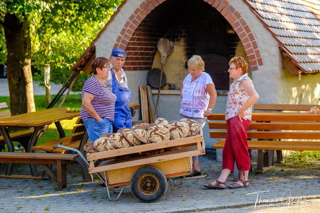 Drei Frauen und ein Mann mit frisch gebackenen Holzofenbroten im Vordergrund
