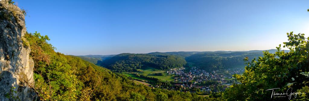 Panoramaaufnahme fränkischer Alblandschaft, Mittelgebirge mit Dorf im Tal.