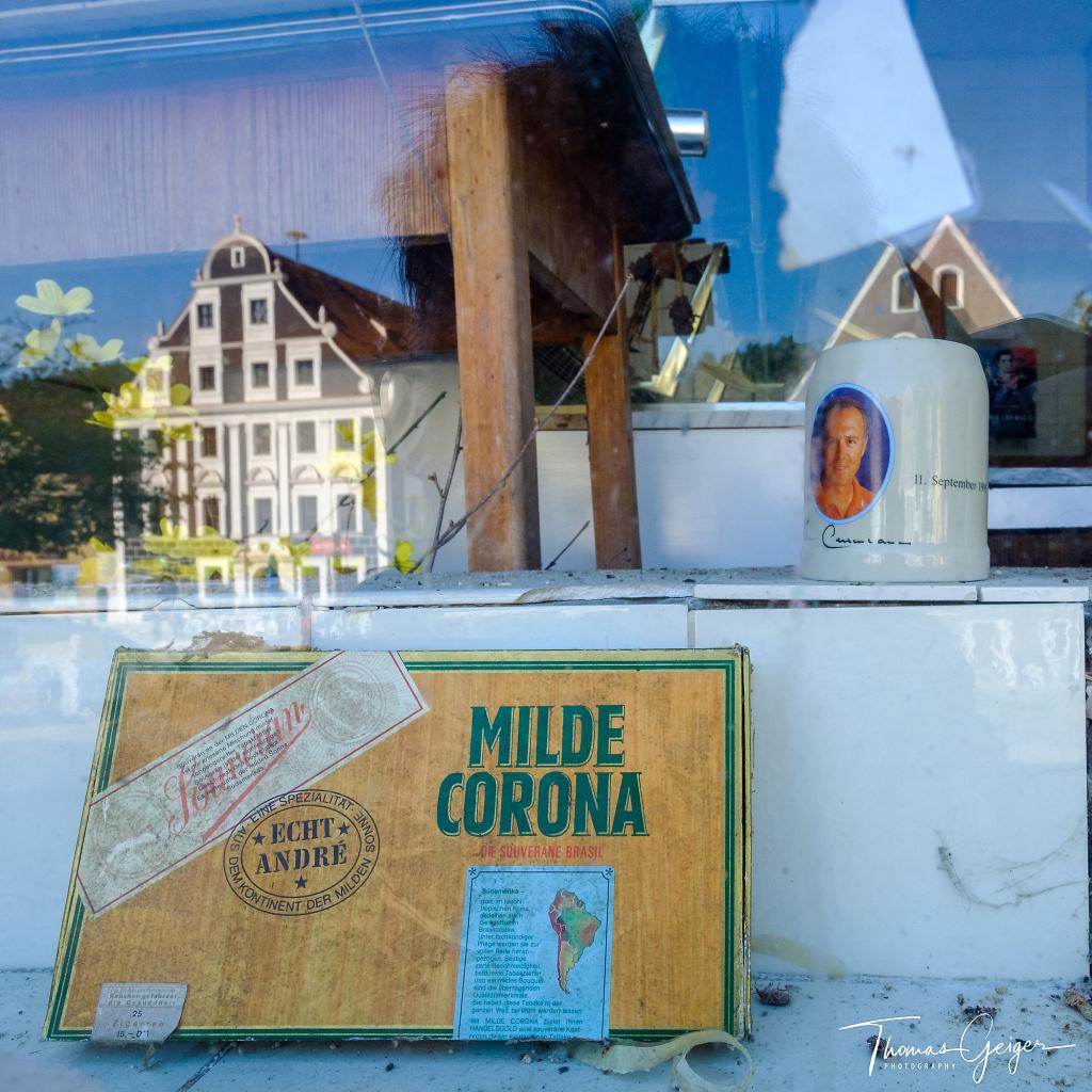 """Zigarrenkiste mit Aufschrift """"Milde Corona"""" in einem Schaufenster in dem sich das Rathaus spiegelt und auch ein Bierkrug mit dem Portrait von Franz Beckenbauer 1995 steht"""