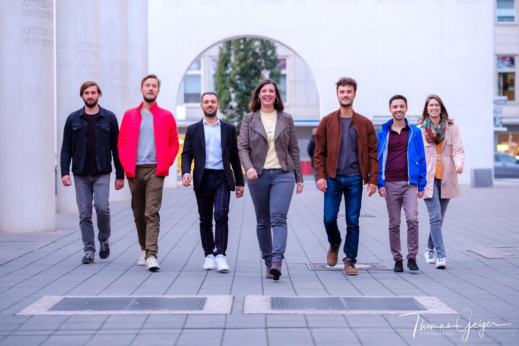 zwei junge Frauen und fünf junge Männer laufen freudig lächelnd auf die Kamera zu