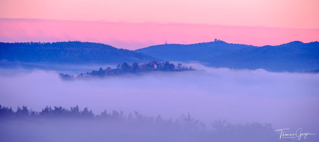 Morgenrot am Himmel über Mittelgebirgslandschaft mit Morgennebel aus dem die Berggipfel ragen.