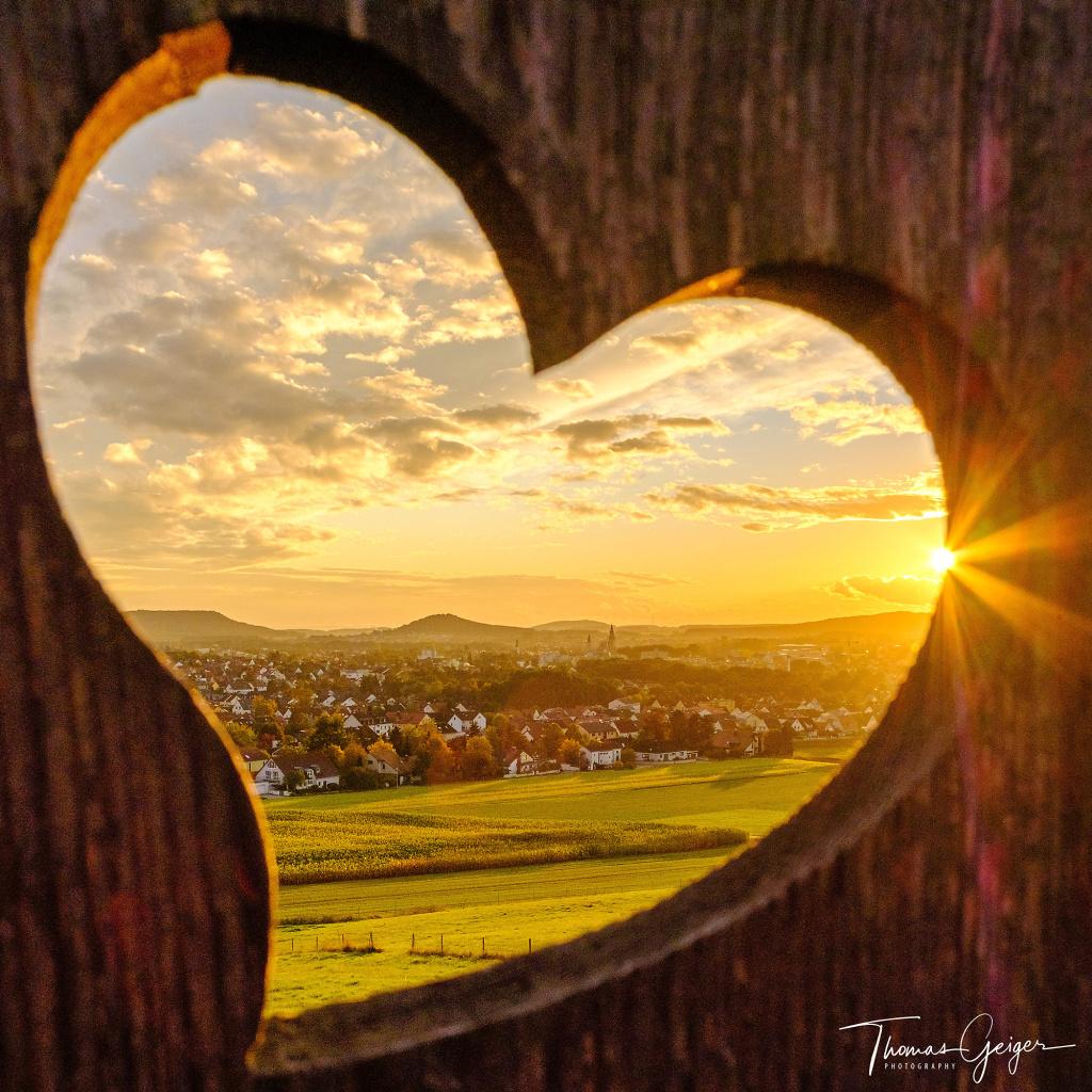 Blick durch einen herzförmigen Ausschnitt in einem Holzzaun auf den Sonnenuntergang über Neumarkt, Die Strahlen der Sonne brechen sich im Ausschnitt.