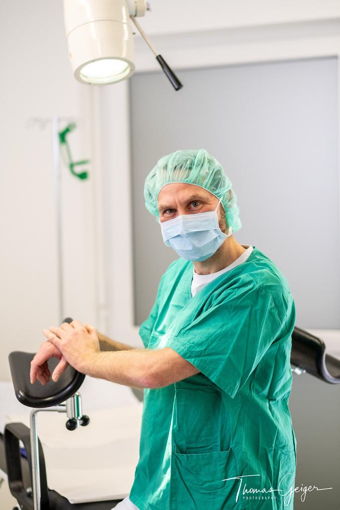 Arzt im OP-Kittel mit Maske und Haube an einen gynäkologischen Stuhl gelehnt