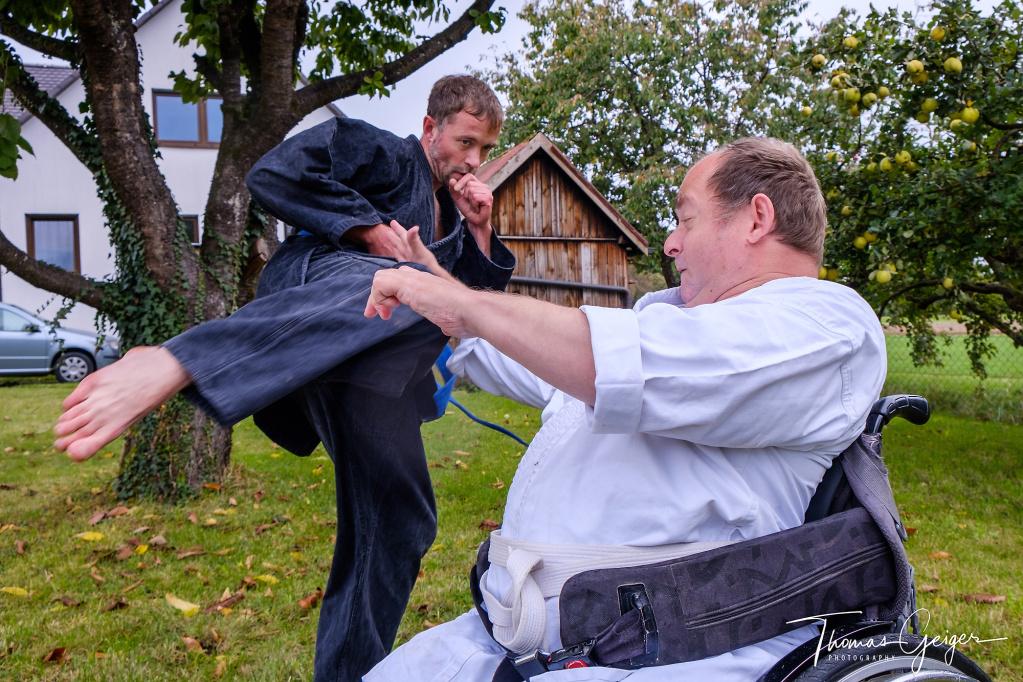 Ein Mann im weißen Karate-Anzug sitzt im Rollstuhl und wehrt den Fusstritt seines Trainingspartners im schwarzen Karate-Anzug ab.