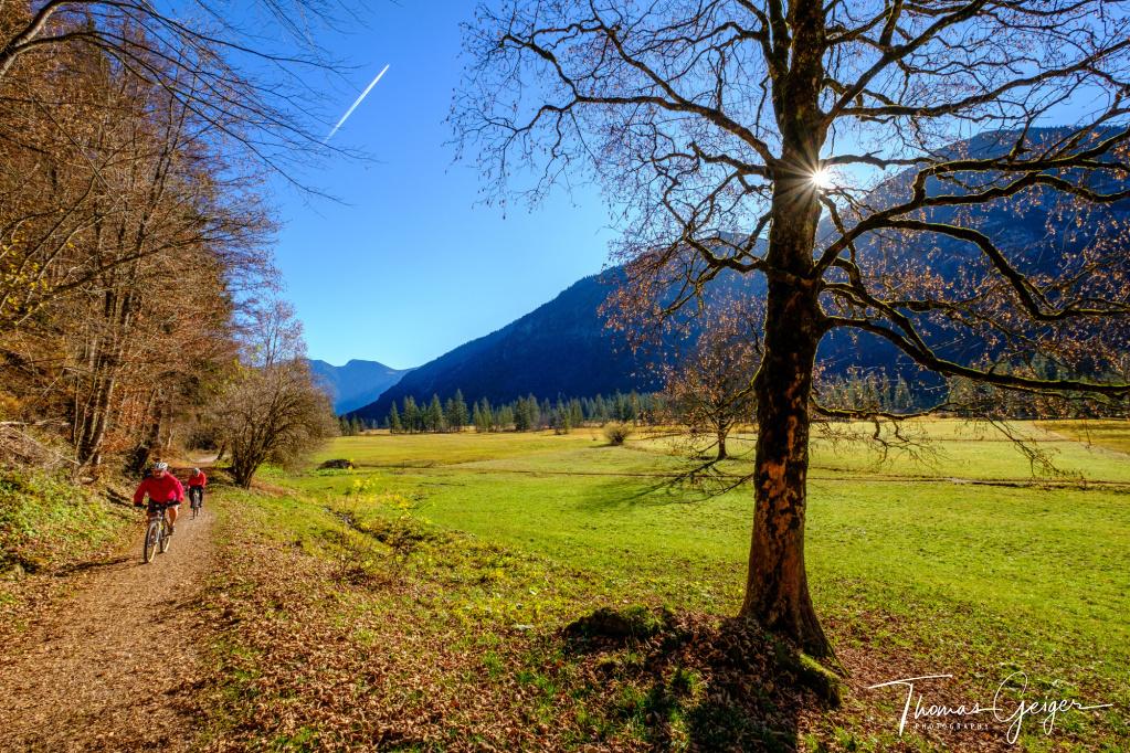 Herbstlandschaft in einem Hochtal in den Bergen, die Sonne spitzt hinter einem Baum hervor, ein Flugzeug zieht am Himmel einen Kondensstreifen, Radfahrer in roter Kleidung fahren am linken Bildrand