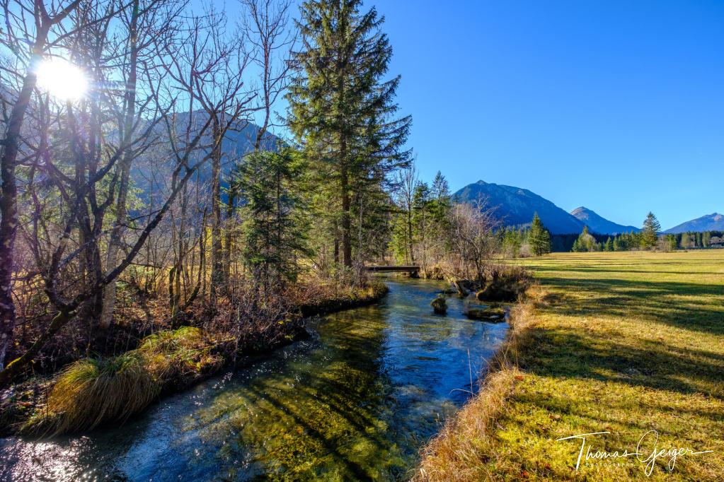 Herbstlandschaft in einem Hochtal in den Bergen, bildmittig ein Bachlauf, die Sonne bricht durch die Bäume