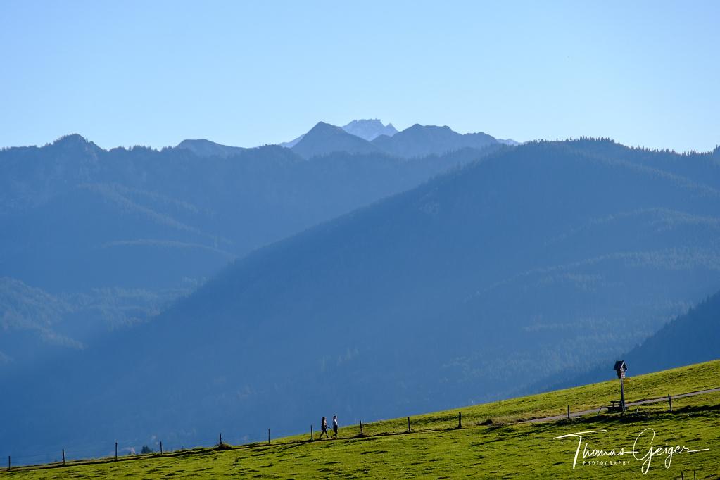 Zwei Wanderer laufen in der Sonne auf ein Marterl zu, dahinter Bergpanorama