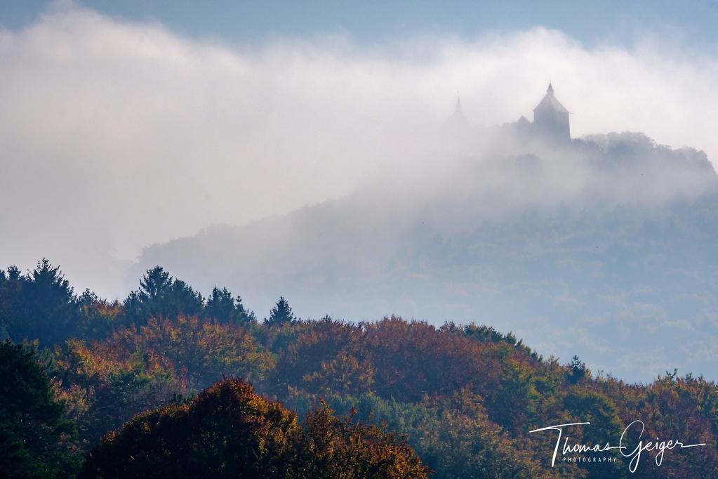 Die Silhouette einer Burg taucht aus dem Nebel auf